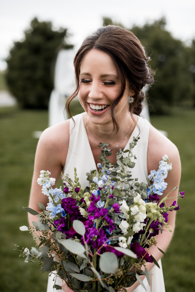 Bride laughing in outdoor portrait with bouquet