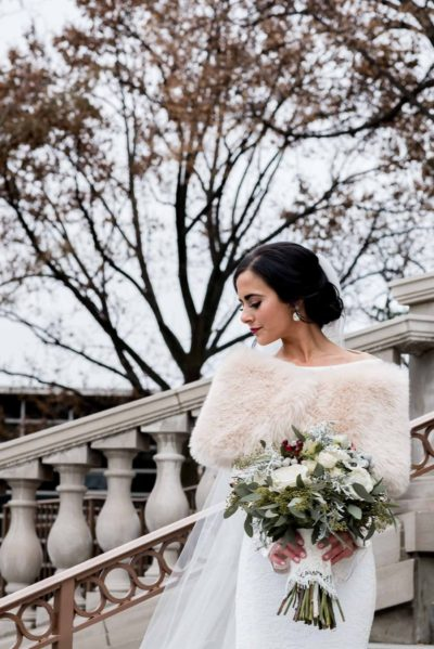 bride with bouquet and fur shrug on steps