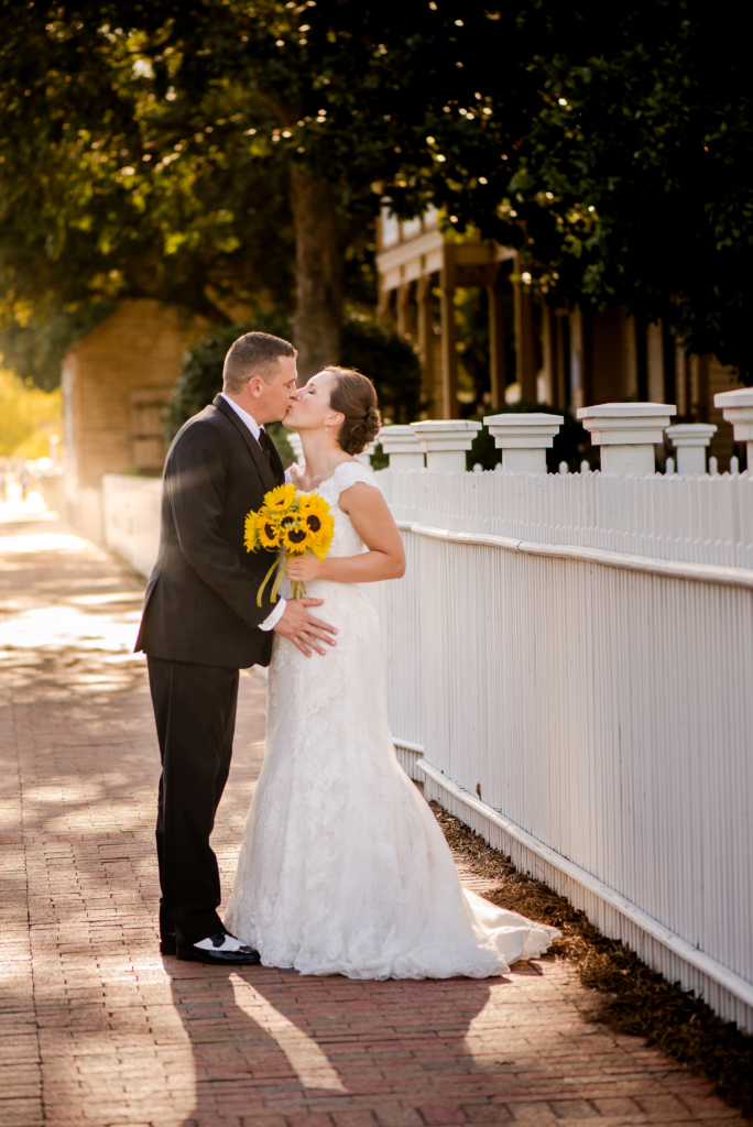 Kissing bride and groom on sidewalk with sunflower bouquet