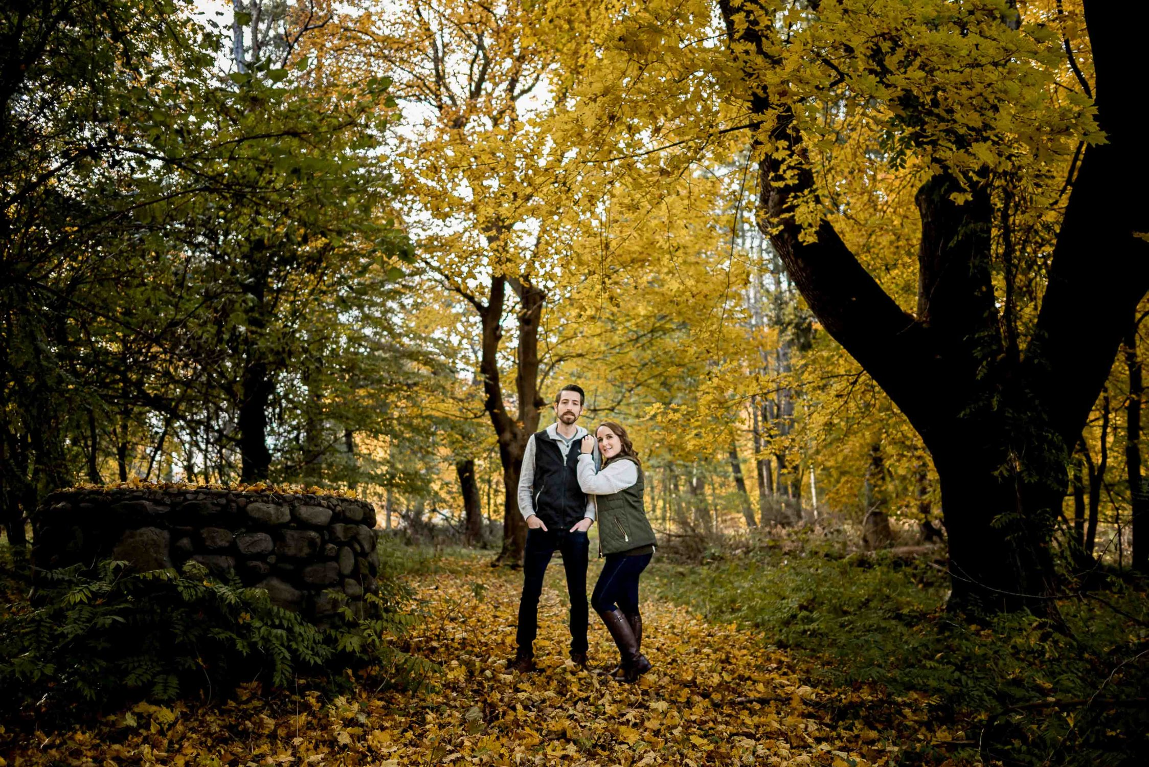 Fall golden yellow leaves with couple on path by old well